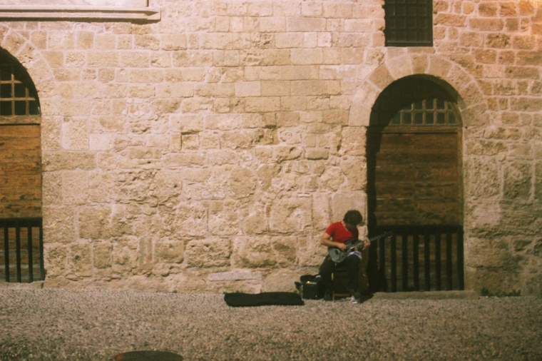 rhodes old town walls exterior cobble streets night guitar musician busker