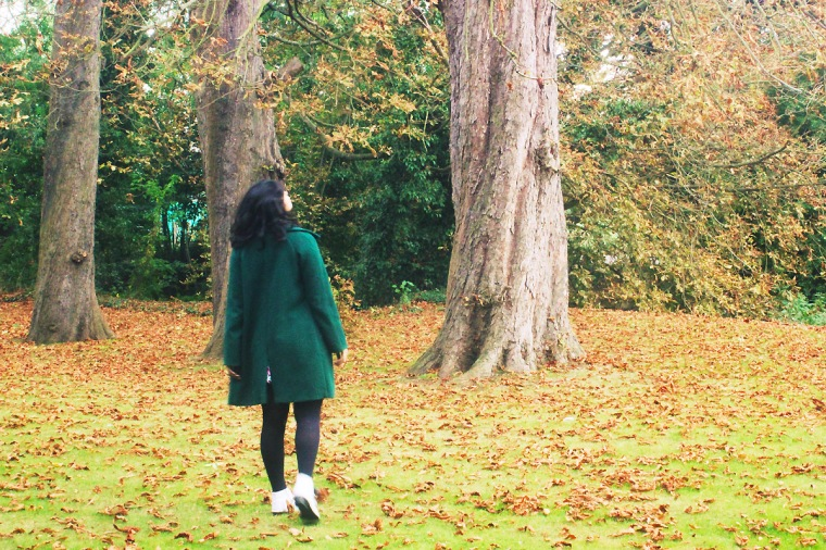 girl in the woods autumn forest trees outdoors exterior green coat flower floral dress